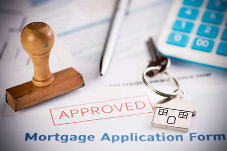 Photo pour An approved Mortgage loan application form with house key and rubber stamp close up - image libre de droit
