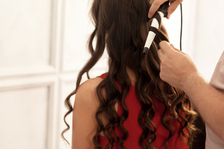 Photo pour Hairstylist curling hair client in hairdressing salon - image libre de droit