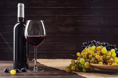 Photo pour Wine bottle and grape on wooden table - image libre de droit