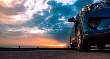 Photo for Blue compact SUV car with sport and modern design parked on concrete road by the sea at sunset. Environmentally friendly technology. Business success concept. - Royalty Free Image