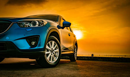 Foto de Blue compact SUV car with sport and modern design parked on concrete road by the sea at sunset. Environmentally friendly technology. Business success concept. - Imagen libre de derechos