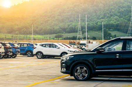 Photo pour Black, white and blue new car parked on concrete parking area at factory near the mountain. Car dealership concept. Car stock for sale. Car factory parking lot. Automotive Industry concept. - image libre de droit