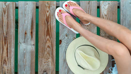 Photo for Young Asian woman with red pedicure wearing pink and white sandals sit on wooden bridge and put hat beside legs on holiday. Summer vacation. Summer vibes. Woman travel alone. Happy backpacker girl. - Royalty Free Image
