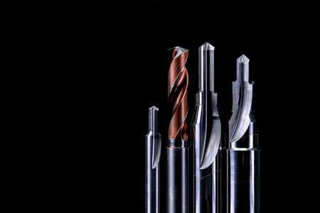 Foto de Special tools isolated on dark background. Made to order special tools. Coated step drill and reamer detail. HSS cemented carbide. Carbide cutting tool for industrial applications. Engineering tools. - Imagen libre de derechos