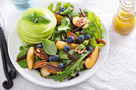 Photo for Fresh healthy salad with leafy greens, plums, nuts and apple - Royalty Free Image