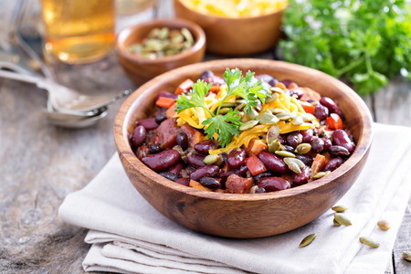 Photo pour Vegetarian chili with red and black beans, cheddar and pumpkin seeds - image libre de droit