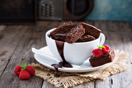 Photo for Brownies in stacked coffee cups with hot fudge chocolate sauce - Royalty Free Image