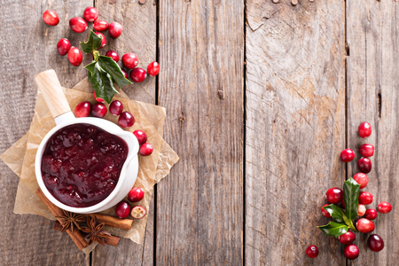 Photo for Cranberry sauce in ceramic saucepan on dark background - Royalty Free Image
