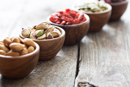 Photo for Variety of nuts and dried fruits in small wooden bowls - Royalty Free Image