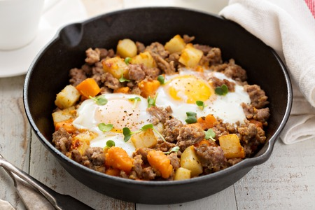 Photo for Potato and sweet potato hash with eggs in cast iron pan - Royalty Free Image