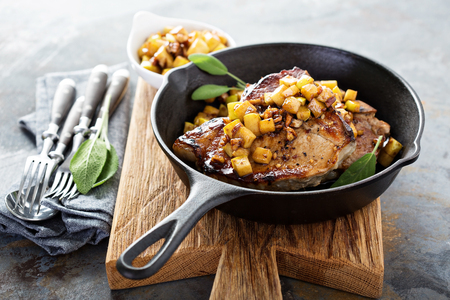 Photo for Sauteed pork chops with caramelized apples and walnuts in a cast iron pan - Royalty Free Image