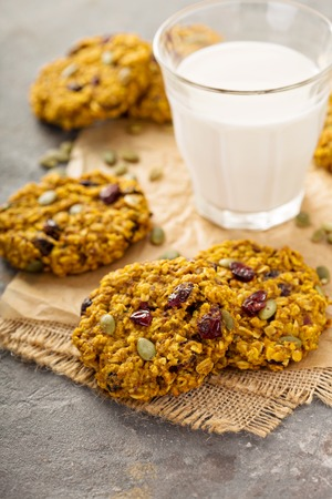 Photo for Breakfast oatmeal cookies with pumpkin puree, cranberry and seeds with milk - Royalty Free Image