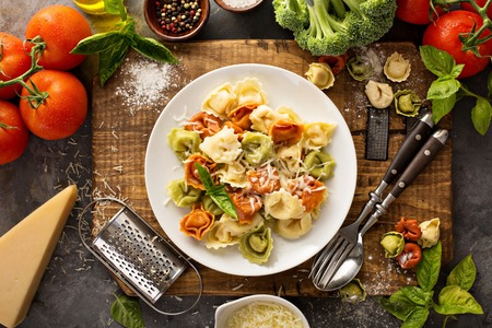 Photo for Red, white and green tortellini with vegetables and cheese - Royalty Free Image