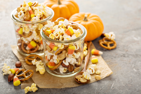 Photo for Homemade Halloween trail or snack mix with candycorn, popcorn, pretzels and nuts in glass jars - Royalty Free Image