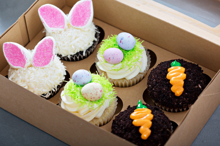 Photo for Assortment of easter cupcakes in a box with bunny ears and candy eggs - Royalty Free Image