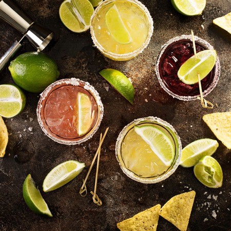 Photo pour Variety of margarita cocktails with salted rim and lime on dark background overhead shot - image libre de droit