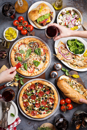 Photo pour Big dinner with pizza, salad and sandwiches with hands reaching food overhead view - image libre de droit