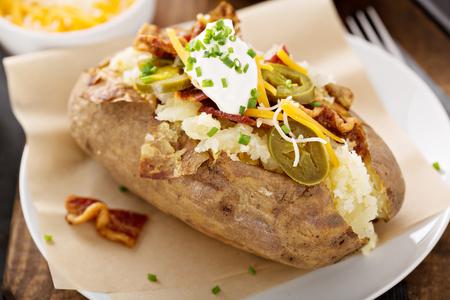Foto de Loaded baked potato with bacon and cheese - Imagen libre de derechos
