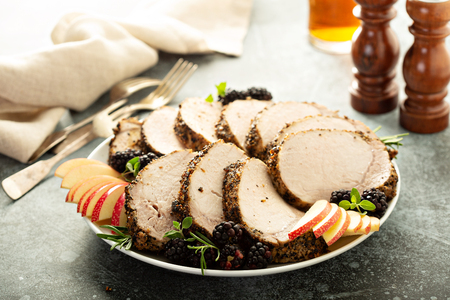 Photo for Roasted pork loin with dry rub sliced on a plate - Royalty Free Image