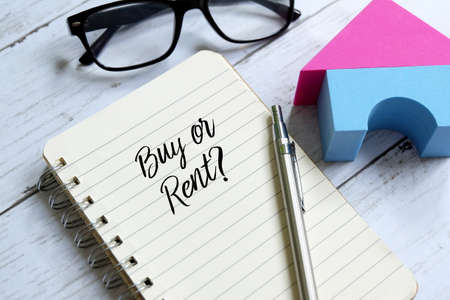 Photo pour Sunglasses,home model,pen and notebook written 'BUY OR RENT?' on white wooden background. - image libre de droit