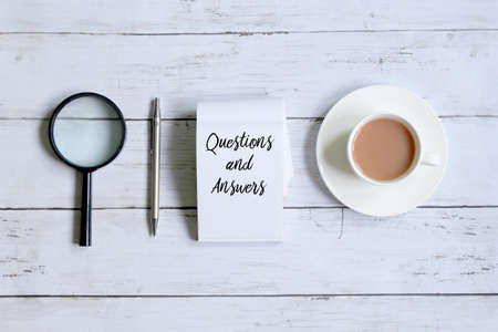 Foto de Top view of a cup of coffee,magnifying glass,pen and notepad written with 'QUESTIONS AND ANSWERS' on white wooden background. - Imagen libre de derechos