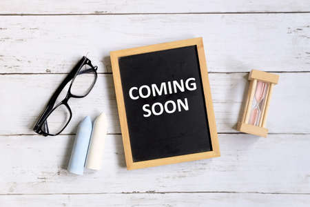 Photo pour Top view of sunglasses,chalk,hourglass and blackboard written with 'COMING SOON' on white wooden background. - image libre de droit
