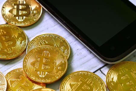 Photo pour Cryptocurrency theme. Golden bitcoin replica with mobile phone. Business and finance concept. - image libre de droit