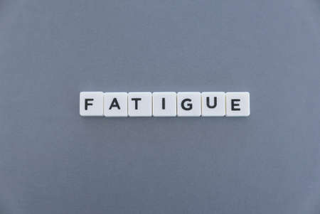 Foto de Fatigue word made of square letter word on grey background. - Imagen libre de derechos
