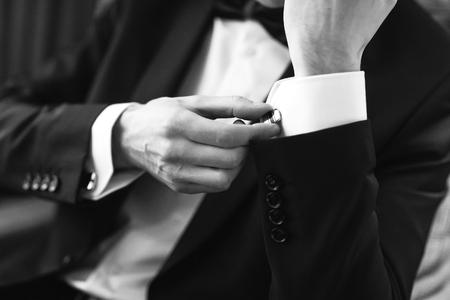 Foto de Confident man buttons cufflinks. Cufflinks closeup. Men's suit, tuxedo. - Imagen libre de derechos