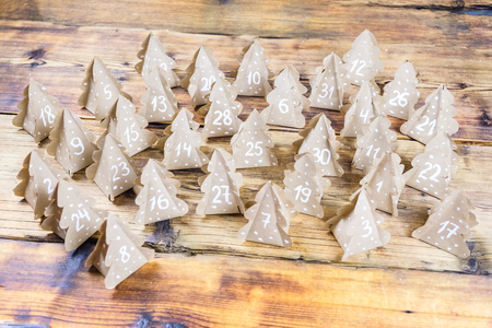 Photo pour Handmade Christmas advent calendar Christmas trees Kraft paper with numbers in wood background. - image libre de droit