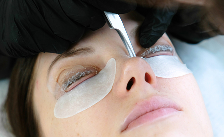 Photo pour Beauty treatment. Cosmetologist removes the solution from the lashes with tweezers. lash lamination. Closeup face. - image libre de droit