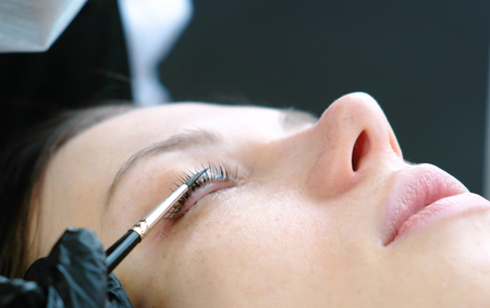Photo pour Cosmetologist rubs the clients eyelash with brush. lash lamination. Closeup eyes. - image libre de droit