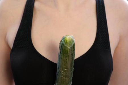Photo pour Closeup womans hands with dress the condom on cucumber. - image libre de droit