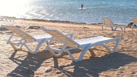 Foto de Two plastic white sunlongers on the sand beach near the sea. - Imagen libre de derechos