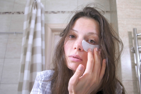 Foto de Tired woken woman with a hangover puts patches on the eyes in the bathroom. - Imagen libre de derechos