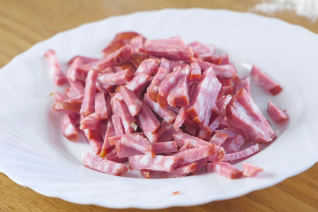 Foto de Close-up view of white plate with cutting smoked sausage of pieces - Imagen libre de derechos