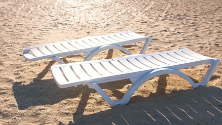 Foto de Two sunlongers on the sand beach in summer. - Imagen libre de derechos