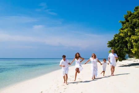 Foto de Family of five celebrating a wedding anniversary running on a beautiful tropical beach  - Imagen libre de derechos