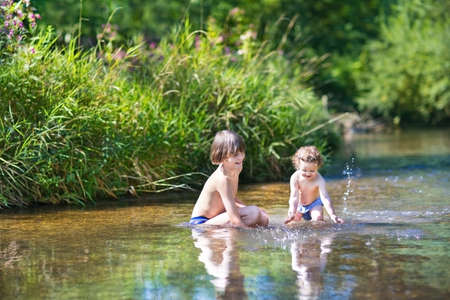 Photo for Young cute boy and his little baby sister playing in the water in a beautiful river on a sunny summer day  - Royalty Free Image