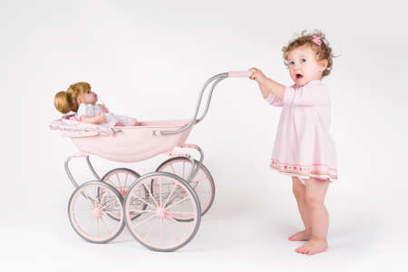 Photo for Funny baby girl walking with a doll stroller  - Royalty Free Image