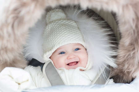 Foto de Happy laughing baby girl in a warm stroller wearing a winter jacket and a hat on a walk in a park  - Imagen libre de derechos