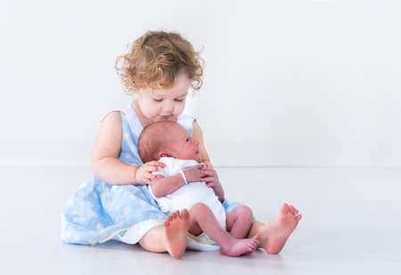 Adorable toddler girl in a blue dress with curly hair holding her newborn baby brother
