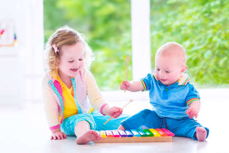 Photo for Two little children - cute curly toddler girl and a funny baby boy, brother and sister playing music, having fun with colorful xylophone at a window - Royalty Free Image