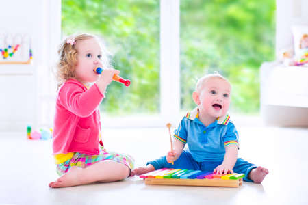 Photo pour Two little children - cute curly toddler girl and a funny baby boy, brother and sister playing music, having fun with colorful xylophone and flute at a window - image libre de droit