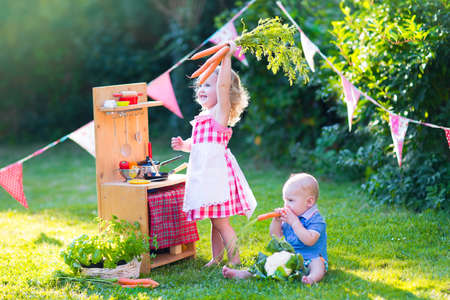 Photo pour Funny curly little girl and adorable baby boy, cute brother and sister, playing together with a vintage wooden toy kitchen, table ware and fresh healthy vegetables in a sunny summer garden - image libre de droit