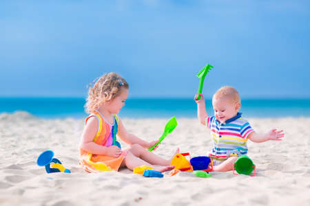Foto de Happy baby boy and little curly toddler girl, brother and sister, playing with toy buckets and plastic shovel digging in sand on a beautiful exotic tropical beach with turquoise water  - Imagen libre de derechos