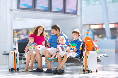 Photo pour Big happy family with three kids travelling by airplane at Dusseldorf International airport, young parents with teenager boy, toddler girl and little baby holding colorful luggage for summer beach vacation - image libre de droit