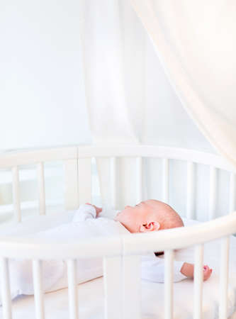 Photo pour Portrait of a newborn baby boy sleeping in a white round crib with canopy   - image libre de droit