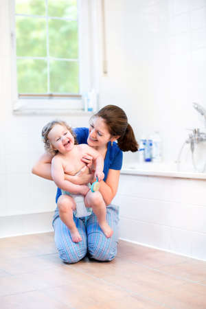 Photo pour Young mother and her happy baby playing together in a white sunny bath room with a garden view window   - image libre de droit