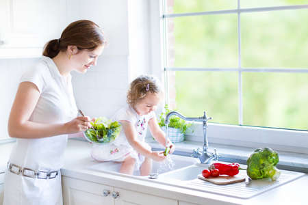 Foto de Young mother and her adorable toddler daughter cooking salad together in a beautiful white kitchen with a big garden view window   - Imagen libre de derechos